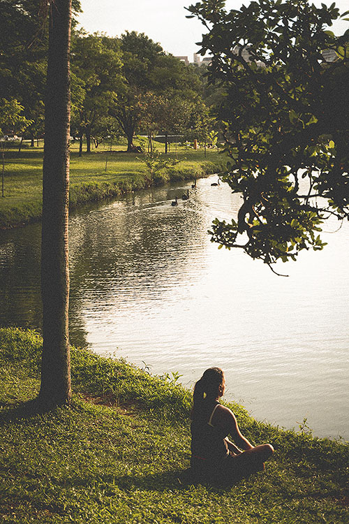 woman sitting on the grass by a lake